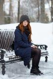 年轻可爱的红头发人妇女美丽的冬天画象在获得逗人喜爱的被编织的帽子的冬天乐趣坐长凳多雪的公园 图库摄影