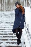 年轻可爱的红头发人妇女美丽的冬天画象在获得逗人喜爱的被编织的帽子的冬天在多雪的公园楼梯的乐趣 库存图片