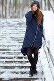 年轻可爱的红头发人妇女美丽的冬天画象在获得逗人喜爱的被编织的帽子的冬天在多雪的公园楼梯的乐趣 免版税库存照片