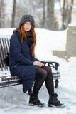 年轻可爱的红头发人妇女美丽的冬天画象在获得逗人喜爱的被编织的帽子的冬天乐趣坐长凳多雪的公园 免版税库存照片