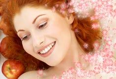 可爱的红头发人用红色苹果和花 免版税库存照片