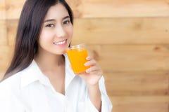 可爱的美丽的亚裔妇女喝橙汁 魅力 库存图片