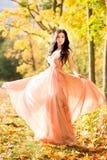 可爱的美丽的妇女 自然,秋天,落黄色叶子 时尚橙色礼服 库存照片