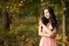 可爱的美丽的妇女 自然,秋天,落黄色叶子 时尚橙色礼服 免版税库存图片