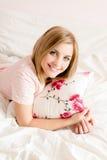 可爱的美丽的愉快的年轻白肤金发的妇女在与花卉枕头在手中愉快的微笑的&看的照相机的床上 免版税库存图片