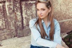 可爱的美丽的柔和的女孩在城市坐老大厦的步在牛仔裤和时尚鞋类的 免版税库存照片