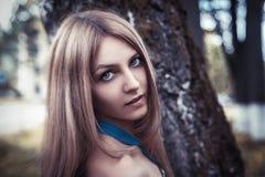 年轻可爱的美丽的白肤金发的女孩在夏天公园 免版税图库摄影