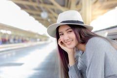 可爱的美女等火车旅行在城市附近 库存照片