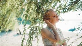 可爱的美妙的未婚轻轻地调直她的从金发的发型有她的手指的,在她发光的立场 影视素材