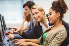 可爱的老师谈话与她的计算机类的学生 免版税图库摄影