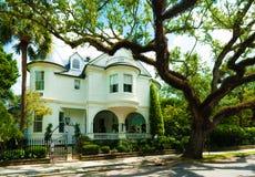 可爱的老庄园住宅在安静的郊区街道上的晴朗的天空下 库存图片