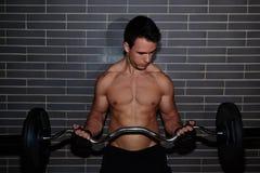 可爱的肌肉修造运动员举的杠铃 免版税库存照片