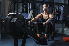可爱的肌肉妇女CrossFit教练员做在室内划船者的锻炼 库存照片