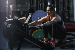可爱的肌肉妇女CrossFit教练员做在室内划船者的锻炼 免版税库存图片