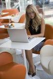 可爱的膝上型计算机妇女运作的年轻人 免版税库存照片