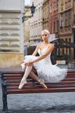 可爱的芭蕾舞女演员坐长凳在城市 免版税图库摄影