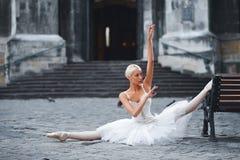 可爱的芭蕾舞女演员坐长凳在城市 库存图片