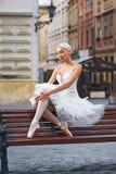 可爱的芭蕾舞女演员坐长凳在城市 图库摄影