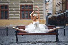 可爱的芭蕾舞女演员坐长凳在城市 库存照片
