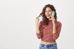 可爱的苗条女性室内射击有卷曲发型和红色唇膏的谈话在智能手机,感人的卷毛 免版税库存图片