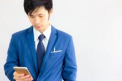 可爱的英俊的商人为searchi使用智能手机 图库摄影