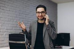可爱的英俊的年轻深色的有胡子的微笑的行政工作者人在事务驻地职场,谈话电话的 库存照片