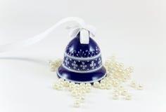 可爱的蓝色陶瓷响铃和白色小珠 免版税库存图片