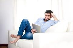 年轻可爱的西班牙人在家使用数字式片剂或垫的白色长沙发的 免版税库存照片