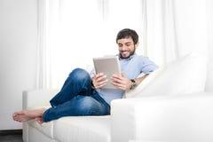 年轻可爱的西班牙人在家使用数字式片剂或垫的白色长沙发的 免版税库存图片