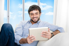 年轻可爱的西班牙人在家坐白色长沙发使用数字式片剂 免版税库存照片