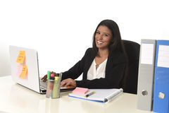 可爱的西班牙女实业家在运转的办公桌坐计算机膝上型计算机微笑愉快 免版税库存照片