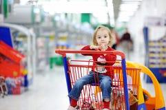可爱的购物车购物坐的小孩 图库摄影
