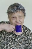 可爱的资深从一个蓝色杯子的妇女饮用的咖啡 免版税图库摄影