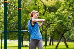 年轻可爱的运动的女孩巧妙的手表脉冲米在公园 伸手 库存照片