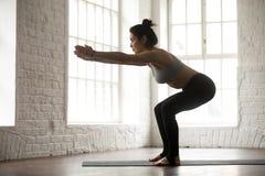 年轻可爱的运动的妇女实践的蹲坐,白色顶楼螺柱 免版税图库摄影