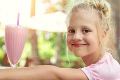 可爱的逗人喜爱的啜饮新鲜美草莓奶昔coctail的学龄前儿童白种人白肤金发的女孩画象在咖啡馆户外 免版税库存图片