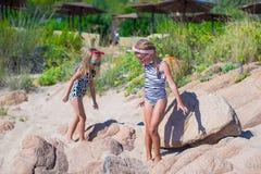 可爱的逗人喜爱的女孩获得在白色海滩的乐趣在期间 库存图片