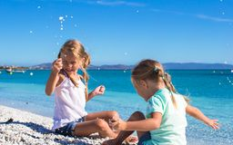 可爱的逗人喜爱的女孩获得在白色海滩的乐趣在期间 免版税库存照片