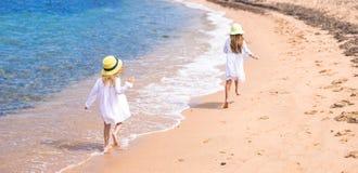 可爱的逗人喜爱的女孩获得在白色海滩的乐趣在期间 库存照片