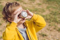 可爱的逗人喜爱的男孩休息的和饮用的茶画象从一个热水瓶的在秀丽秋天公园 免版税库存图片