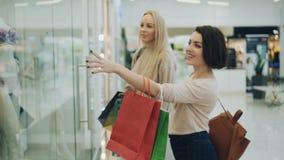可爱的金发碧眼的女人购物与她相当女性朋友聊天的和微笑的走在然后看的购物中心 股票录像