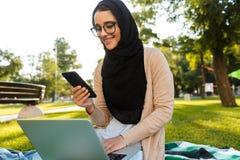可爱的阿拉伯使用银色膝上型计算机的妇女佩带的头巾照片  免版税库存图片