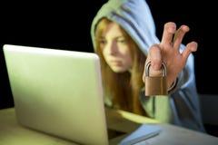 年轻可爱的青少年的乱砍膝上型计算机网络犯罪网络罪行概念的妇女佩带的有冠乌鸦 库存照片