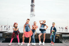 可爱的青少年的女孩创造性的队在公园摆在户外在喷泉附近 免版税库存照片