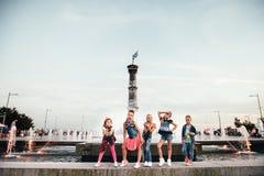 可爱的青少年的女孩创造性的队在公园摆在户外在喷泉附近 免版税库存图片