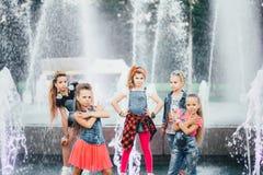 可爱的青少年的女孩创造性的队在公园摆在户外在喷泉附近 免版税图库摄影