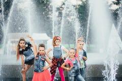 可爱的青少年的女孩创造性的队在公园摆在户外在喷泉附近 图库摄影