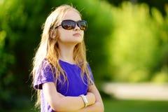 可爱的青春期前的女孩佩带的太阳镜在晴朗的夏日 库存图片