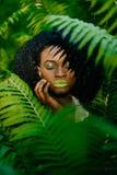 可爱的非洲女孩的敏感室外画象有绿色轻轻地接触她的面孔的唇膏和眼影膏的 图库摄影
