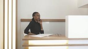 可爱的非洲妇女的画象有自然构成的在招待会 她坐在桌和谈上 免版税库存图片